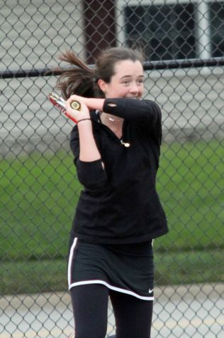Carney is all smiles as she takes a swing to earn the point.