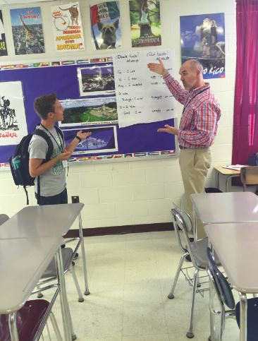 In his 22 years at West, Hawkins has spread his optimism to students. Here, he explains a concept to a Spanish 4 student. Photo by Kelsey Warren.
